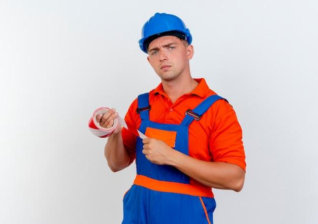 Zuversichtlich junger männlicher baumeister, der uniform und sicherheitshelm hält, der klebeband hält
