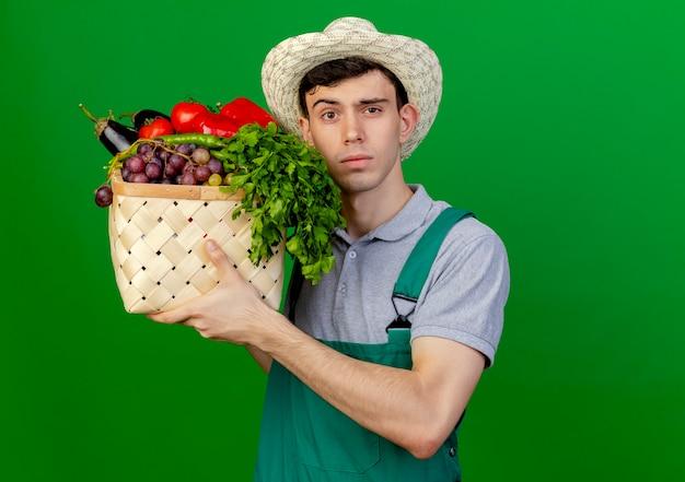 Zuversichtlich junger männlicher gärtner, der gartenhut trägt, hält gemüsekorb lokalisiert auf grünem hintergrund mit kopienraum