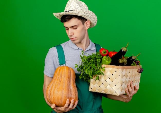 Zuversichtlich junger männlicher gärtner, der gartenhut trägt, hält gemüsekorb und betrachtet kürbis lokalisiert auf grünem hintergrund mit kopienraum