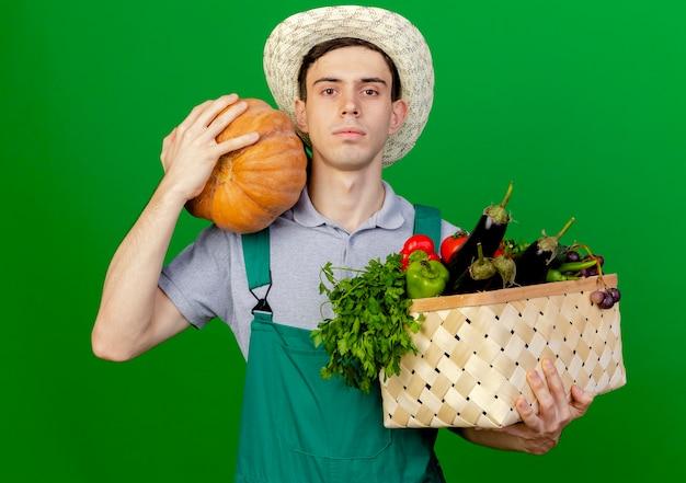 Zuversichtlich junger männlicher gärtner, der gartenhut trägt, hält gemüsekorb und kürbis suchen