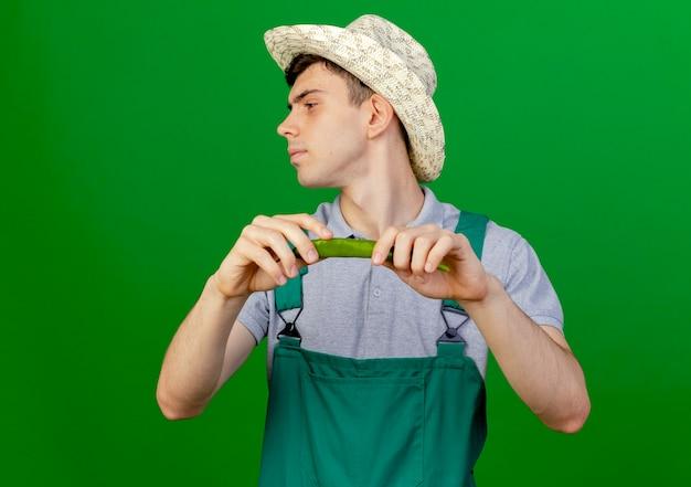Zuversichtlich junger männlicher gärtner, der gartenhut trägt, hält heißen pfeffer, der seite lokalisiert auf grünem hintergrund mit kopienraum betrachtet
