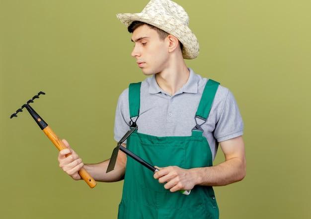 Zuversichtlich junger männlicher gärtner, der gartenhut trägt, hält rechen und hacke, die seite betrachten