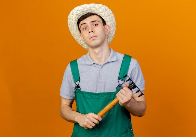 Zuversichtlich junger männlicher gärtner, der gartenhut trägt, hält rechen