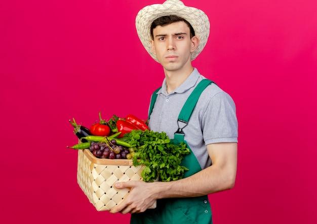 Zuversichtlich junger männlicher gärtner, der gartenhut trägt, steht seitlich und hält gemüsekorb