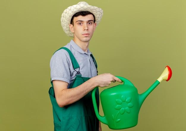Zuversichtlich junger männlicher gärtner, der gartenhut trägt, steht seitlich und hält gießkanne