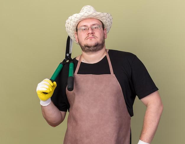 Zuversichtlich junger männlicher gärtner, der gartenhut und handschuhe trägt, die haarschneidemaschine auf schulter halten und hand auf hüfte lokalisiert auf olivgrüner wand setzen