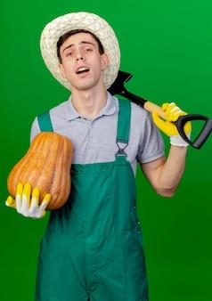 Zuversichtlich junger männlicher gärtner, der gartenhut und handschuhe trägt, hält kürbis und spaten auf schulter lokalisiert auf grünem hintergrund mit kopienraum