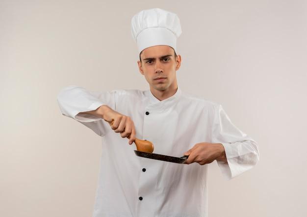 Zuversichtlich junger männlicher koch, der kochuniform trägt, die bratpfanne und löffel auf isolierter weißer wand hält