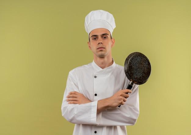 Zuversichtlich junger männlicher koch, der kochuniform trägt, die hände hält, die bratpfanne auf isolierter grüner wand mit kopienraum halten