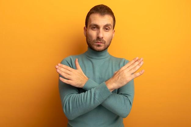Zuversichtlich junger mann, der front betrachtet, hält hände gekreuzt in der luft lokalisiert auf orange wand