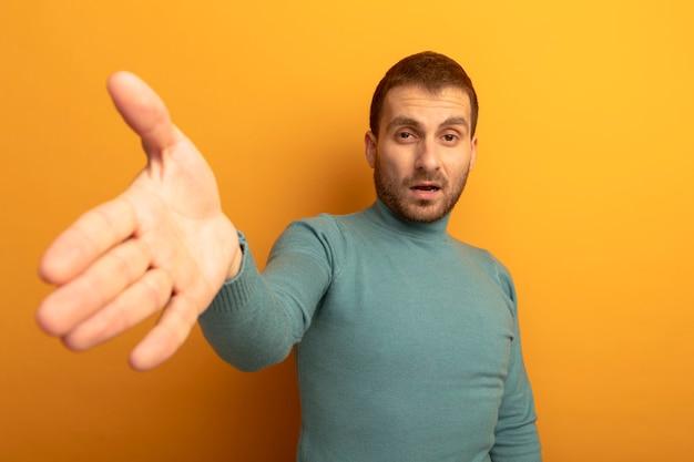 Zuversichtlich junger mann, der front betrachtet, streckt hand in richtung front lokalisiert auf orange wand aus