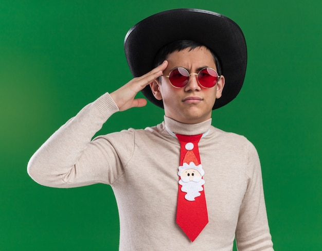 Zuversichtlich junger mann, der hut mit weihnachtskrawatte und brille trägt, die grußgeste lokalisiert auf grüner wand zeigt