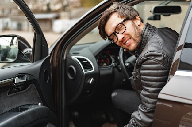Zuversichtlich junger mann, der in einem auto sitzt