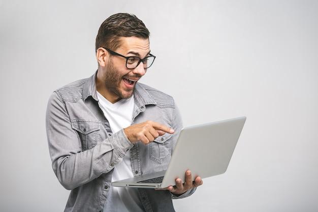 Zuversichtlich junger schöner mann im hemd, das laptop hält und lächelt, während gegen weißen hintergrund stehend