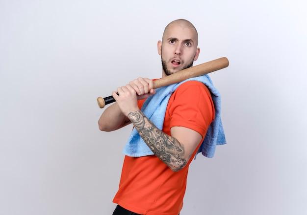 Zuversichtlich junger sportlicher mann, der beisbol gebiss auf schulter und handtuch auf schulter lokalisiert auf weißem hintergrund hält