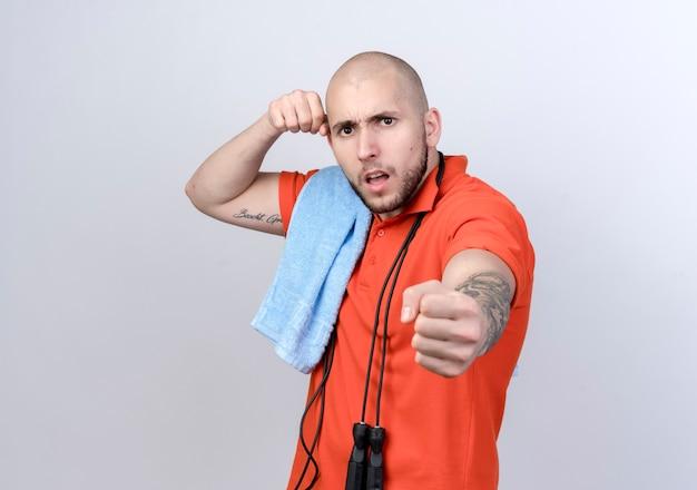 Zuversichtlich junger sportlicher mann, der in der kampfhaltung mit handtuch auf schulter und springseil lokalisiert auf weißer wand steht