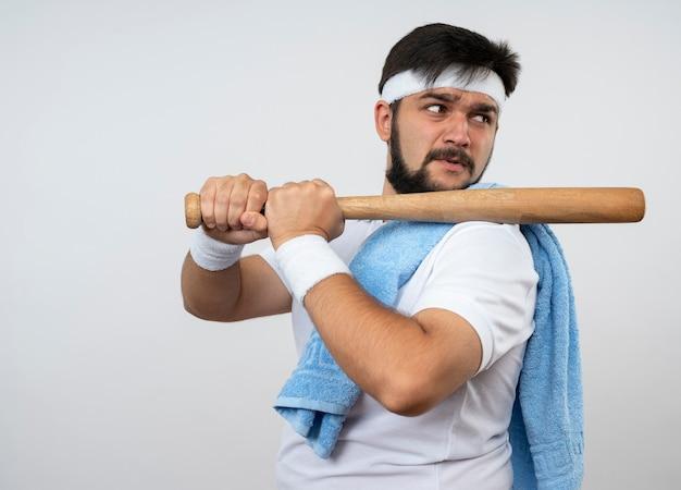 Zuversichtlich junger sportlicher mann, der seite betrachtet, die stirnband und armband mit handtuch auf schulter hält baseballschläger auf schulter lokalisiert auf weißer wand mit kopienraum