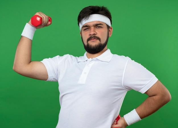 Zuversichtlich junger sportlicher mann, der stirnband und armband hält hantel, die hand auf hüfte lokalisiert auf grün hält