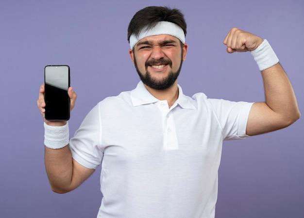 Zuversichtlich junger sportlicher mann, der stirnband und armband hält telefon hält und starke geste zeigt, die auf grün lokalisiert wird