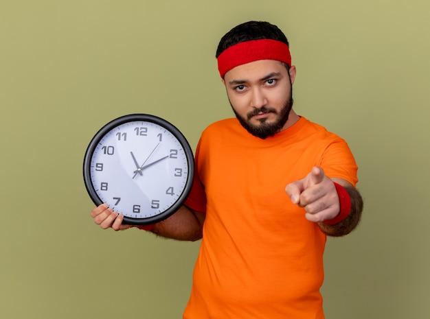 Zuversichtlich junger sportlicher mann, der stirnband und armband hält wanduhr, die sie geste zeigt