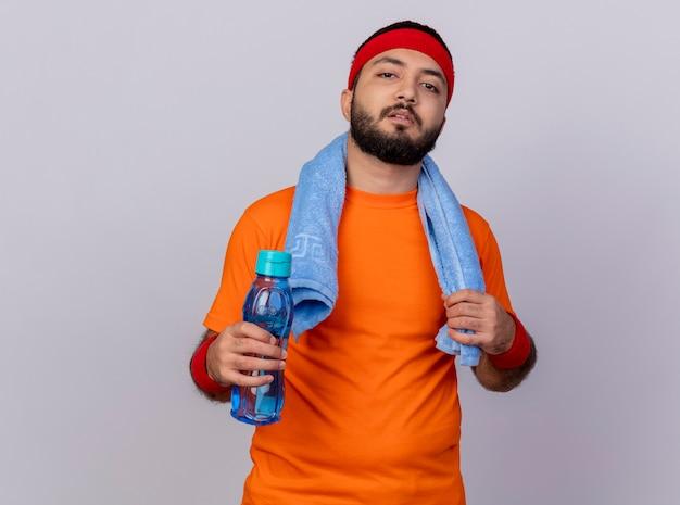 Zuversichtlich junger sportlicher mann, der stirnband und armband hält wasserflasche mit handtuch auf schulter lokalisiert auf weißem hintergrund trägt