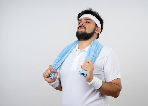 Zuversichtlich junger sportlicher mann, der stirnband und armband mit handtuch auf schulter lokalisiert auf weißer wand mit kopienraum trägt