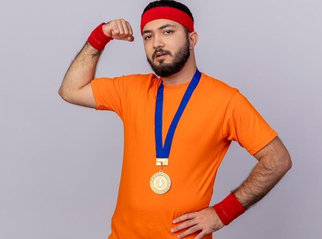 Zuversichtlich junger sportlicher mann, der stirnband und armband mit medaille trägt hand auf hüfte zeigt starke geste lokalisiert auf weißem hintergrund