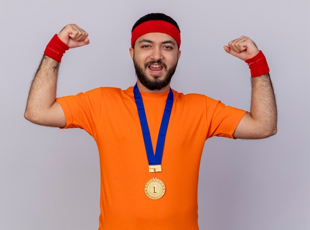 Zuversichtlich junger sportlicher mann, der stirnband und armband mit medaille zeigt, die starke geste lokalisiert auf weißem hintergrund zeigt