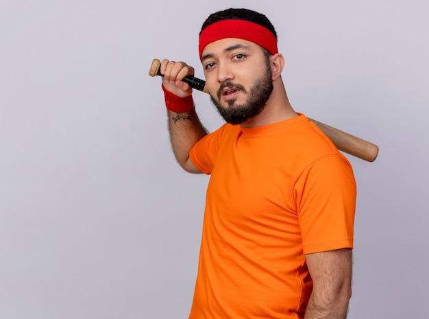 Zuversichtlich junger sportlicher mann, der stirnband und armband trägt baseballschläger auf schulter setzt