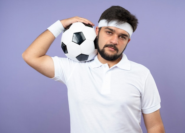 Zuversichtlich junger sportlicher mann, der stirnband und armband trägt, die ball auf schulter setzen