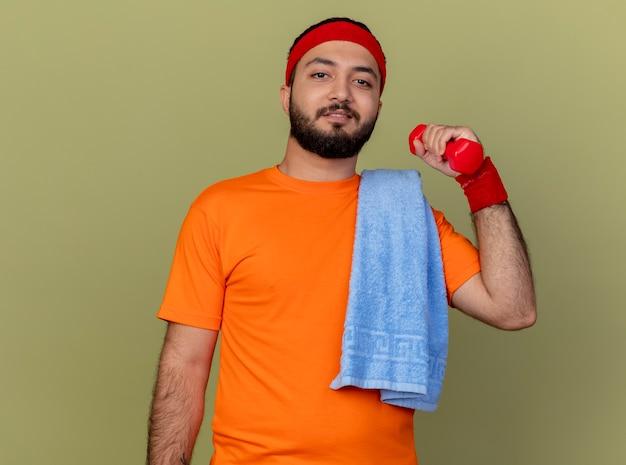 Zuversichtlich junger sportlicher mann, der stirnband und armband trägt, die mit hantel mit handtuch auf schulter lokalisiert auf olivgrünem hintergrund trainieren