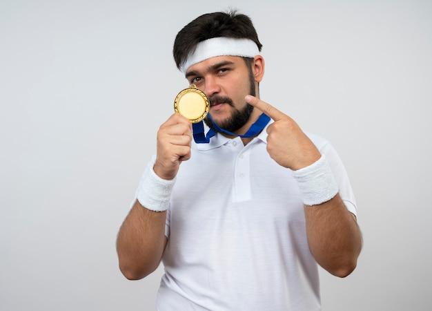 Zuversichtlich junger sportlicher mann, der stirnband und armband trägt und punkte auf medaille lokalisiert auf weißer wand trägt