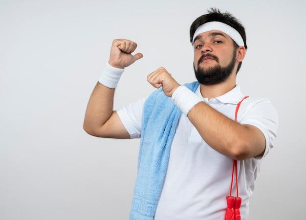 Zuversichtlich junger sportlicher mann, der stirnband und armband zeigt, zeigt hinten mit handtuch am springseil auf schulter lokalisiert auf weißer wand