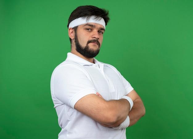 Zuversichtlich junger sportlicher mann, der stirnband und armbandkreuzungshände lokalisiert auf grüner wand trägt