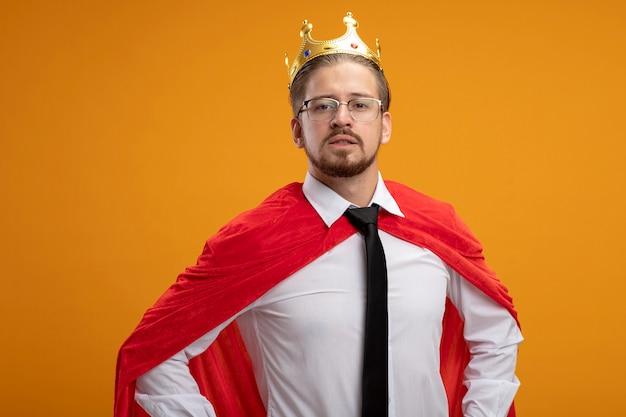 Zuversichtlich junger superheld kerl, der krawatte und krone mit brille trägt, die hände auf hüfte lokalisiert auf orange setzen
