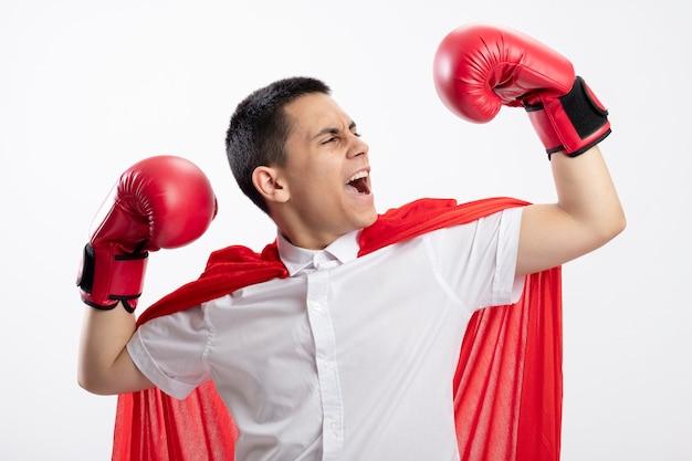 Zuversichtlich junger superheldenjunge im roten umhang, der kastenhandschuhe tut, die starke geste tun, die seine hand betrachtet, die lokal auf weißem hintergrund schreit