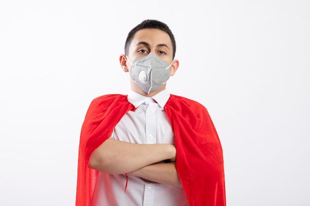 Zuversichtlich junger superheldenjunge im roten umhang, der schutzmaske steht, die mit geschlossener haltung steht und kamera lokalisiert auf weißem hintergrund mit kopienraum betrachtet