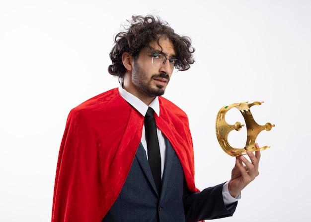 Zuversichtlich junger superheldenmann in optischer brille, die anzug mit rotem umhang trägt, hält krone isoliert auf weißer wand