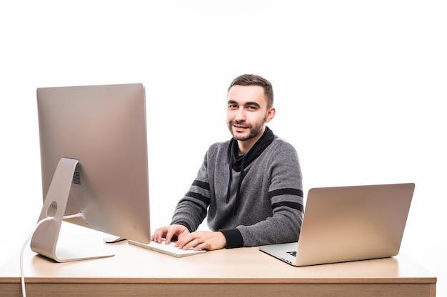 Zuversichtlich junger unternehmer, der am tisch mit laptop und pc sitzt und kamera lokalisiert auf weiß betrachtet