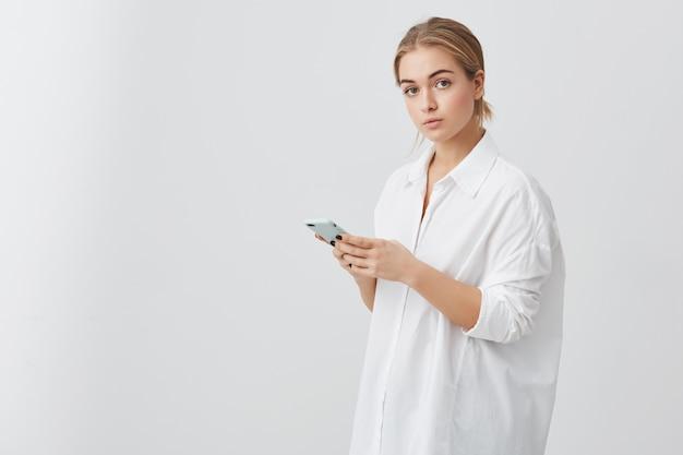 Zuversichtlich kaukasische frau mit hellem haar, das weißes hemd trägt, das nachricht auf smartphone schreibt. porträt der ernsten geschäftsfrau, die aufwirft, handy in ihren händen hält.