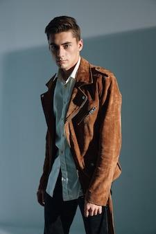 Zuversichtlich kerl in brauner jacke auf grauem hintergrund beschnittene ansicht. hochwertiges foto
