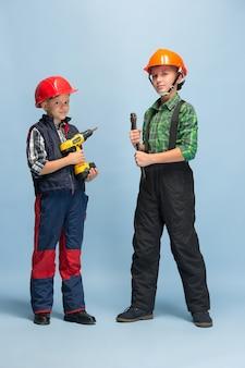 Zuversichtlich. kinder träumen vom beruf des ingenieurs. kindheit, planung, bildung und traumkonzept. willst du erfolgreicher mitarbeiter in der fertigung, bauindustrie, infrastruktur werden.
