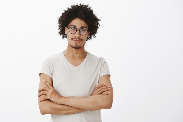 Zuversichtlich kluger mann verschränkt die brust, trägt eine brille und sieht aus wie ein profi
