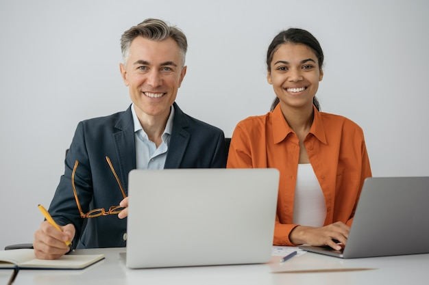 Zuversichtlich kollegen, die laptop verwenden, die im modernen büro zusammenarbeiten.