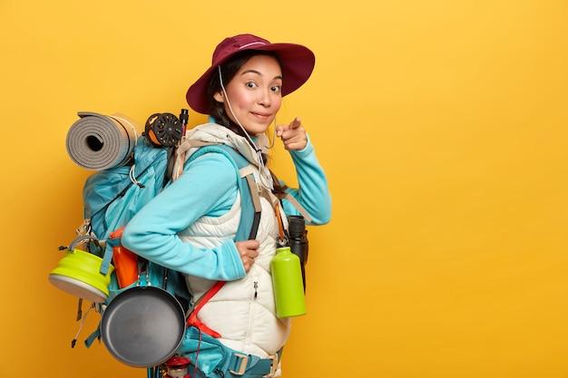 Zuversichtlich koreanische touristenpunkte bei ihnen, bittet um teilnahme an der reise, wandert gerne mit dem rucksack, führt einen gesunden lebensstil, trägt freizeitkleidung, trägt reiseartikel