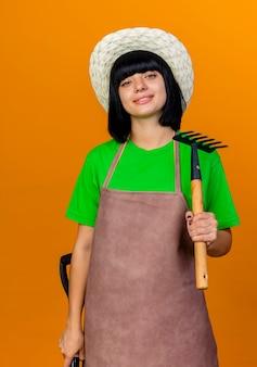 Zuversichtlich lächelnde junge gärtnerin in uniform mit gartenhut hält spaten und rechen