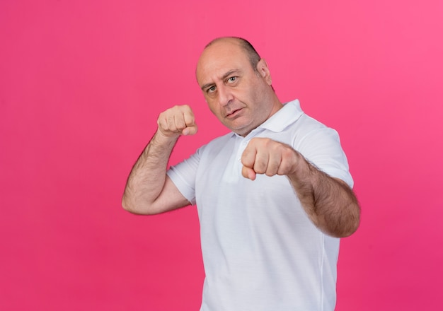 Zuversichtlich lässiger reifer geschäftsmann, der boxgeste an der kamera lokalisiert auf rosa hintergrund mit kopienraum tut