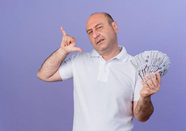 Zuversichtlich lässiger reifer geschäftsmann, der geld hält und lose geste hängt, die auf lila hintergrund lokalisiert wird
