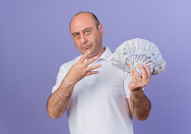 Zuversichtlich lässiger reifer geschäftsmann, der geld hält und vier mit hand lokalisiert auf lila hintergrund mit kopienraum zeigt