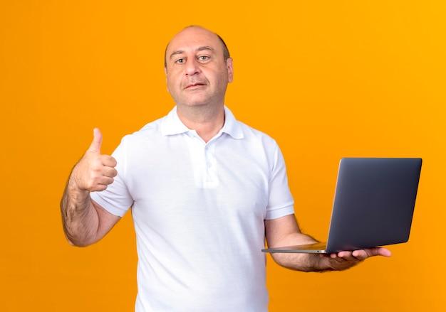 Zuversichtlich lässiger reifer mann, der laptop seinen daumen oben lokalisiert auf gelbem hintergrund hält